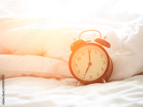 Poster Alarm clock on bed in morning with sun light..