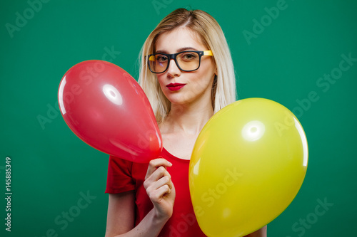 Poster Blonde Wearing Short Red Top and Glasses is Dancing with Two Air Balloons in Her Hands
