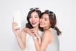 Portrait of two beautiful asian fashionable women taking selfie