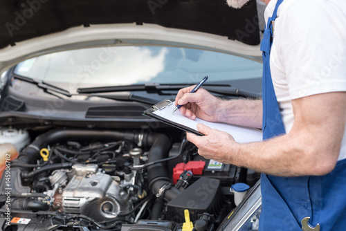 Car mechanic checking a car engine