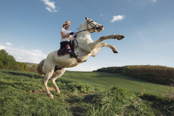 Young female rider, jumping with white horse