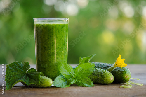 Green smoothie with cucumber and mint as healthy summer drink on wooden background