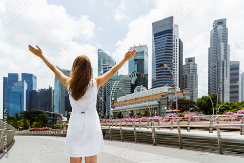 Girl with raised arms to the sky on skyscrapers background