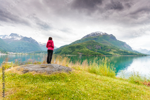 Poster Woman tourist relaxing on fjord sea shore, Norway