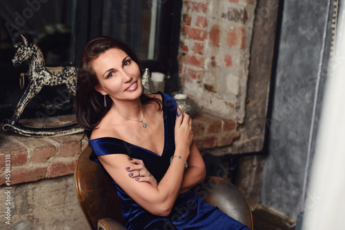 Seductive woman 50 years old posing in photo studio Poster