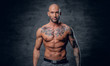 Shaved head, muscular male with tattoos on his torso over grey vignette background.