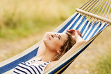 Young blonde woman resting on hammock - 146038160