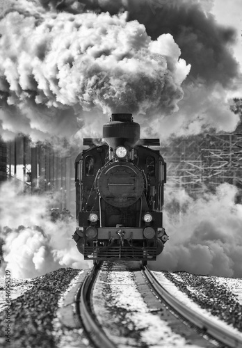 Historic locomotive leaving the station. Retro train on the rails. Sky full of smoke. Image in black and white. - 146045339