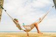 Quadro Woman relaxing at the beach on a hammock
