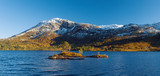 Norwegian autumn landscape – fjord and distant snow-capped mountains, blue clear water and rocky island with pines