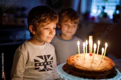 Poster Two beautiful kids, little preschool boys celebrating birthday and blowing candl
