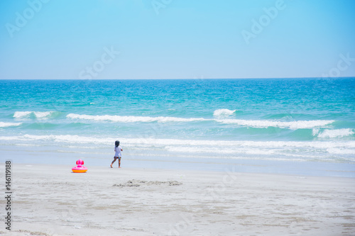 ittle girl playing on the beach blue sea and sky blue Poster