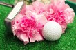 Golf ball with putter are on green grass with carnation flower