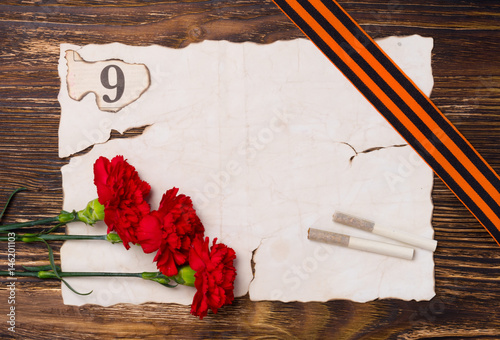 Poster Vintage background for a victory day postcard, with a red carnation, two cigaret
