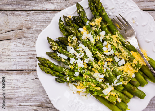 Green asparagus with a yellow sauce on a wooden background.