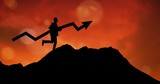 Silhouette businessman with arrow sign on mountain during sunset