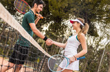 Happy young couple of tennis players shaking hands