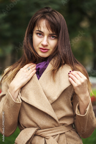 Portrait of a young beautiful woman in beige coat Poster