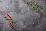Chili pepper and fresh thyme on a gray concrete background, top view