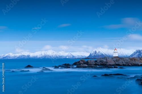 Leuchtturm an der Küste der Lofoten auf Norwegen vor verschneiten Bergen