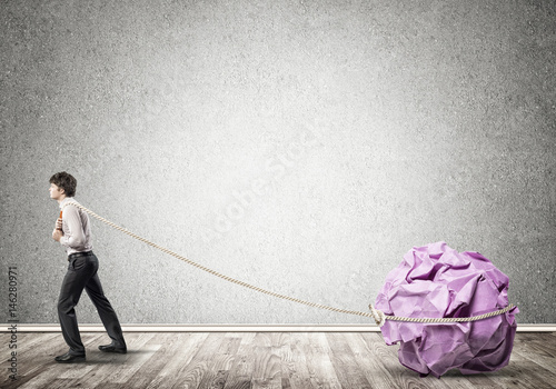 Man pulling with effort big crumpled ball of paper as creativity sign