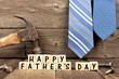 Happy Fathers Day wooden blocks with tools and ties in the background against rustic wood - 146286900