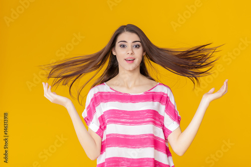 portrait of a cheerful young brunette woman with flying hair on yellow background
