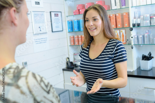 Two women talking over cosmetics counter