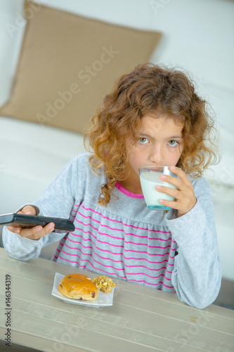 Watching cartoons as he eats breakfast