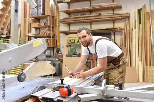 Tischler arbeitet an einer Säge in einer Schreinerei // Carpentry working on a saw in a carpenter's workshop