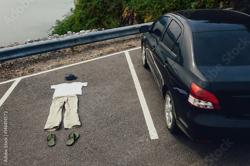 Men's trousers, a T-shirt, a cap and slippers lie on the road next to the car Poster
