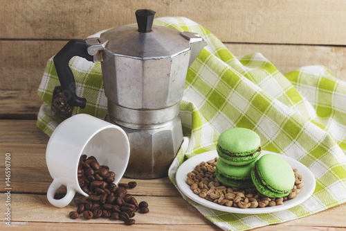 Green macarons on the plate, cup, coffee pot and plaid napkin Poster