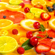 beautiful fresh sliced mixed citrus fruits as background with different berries, concept of healthy eating, dieting, close up