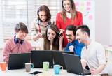 Fototapeta Entwickler in web startup programmieren software und arbeiten dazu gemeinsam am computer
