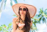 Frau am tropischen Strand wirft einen Luftkuss