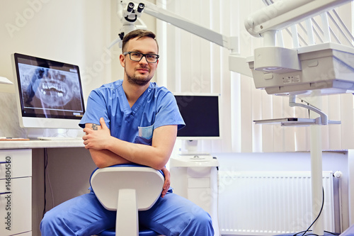 Fototapeta Male dentist in a room with medical equipment on background.