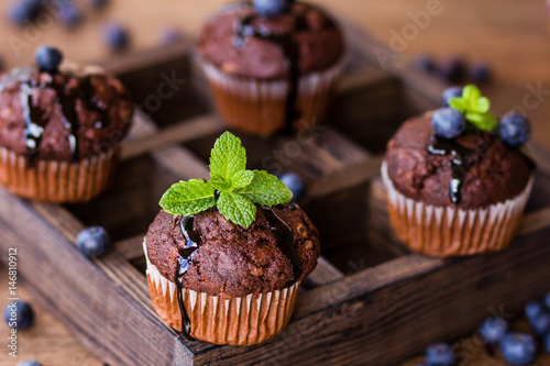 Chocolate muffins with chocolate syrup, blueberries and mint in a wooden backgro Poster