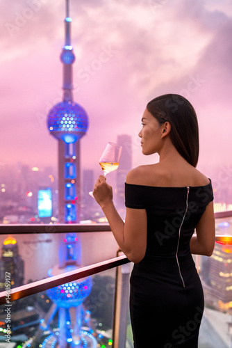 Elegant asian woman in gown drinking white wine glass at rooftop bar terrace looking at city lights skyline view of Shanghai in sunset Poster