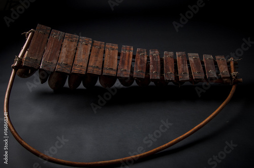 Poster African music instrument, wooden marimba with two bakets, isolated on dark backg