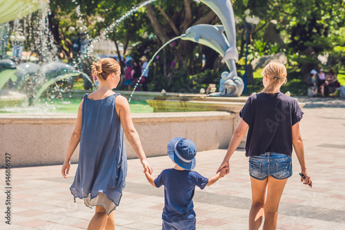 Poster Tourists of a woman and a boy are walking in the amusement park