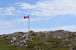 Canadian flag on a barren rocky hill in Newfoundland