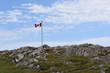 Canadian flag on a barren rocky hill in Newfoundland