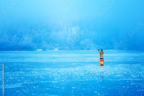 Plagát Woman on ice lake in beautiful ethno dress. Prayer for the lake.