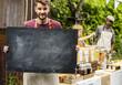 Man holding copyspace blackboard at farmers market festival