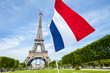 Tricolour French flag flying in blue sky in front of the Eiffel Tower in Paris, France