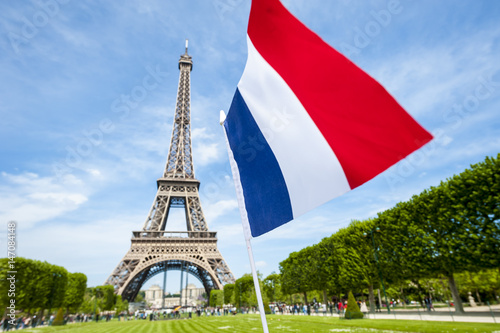 Plagát Tricolour French flag flying in blue sky in front of the Eiffel Tower in Paris,