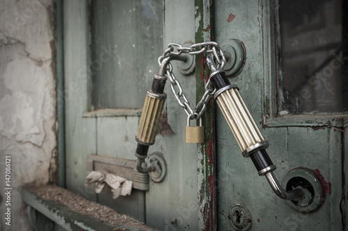 old wooden door locked with a padlock and a chain Poster