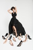 Inside the Studio woman in black dress with gorgeous long dark hair among the shoes. - 147086755