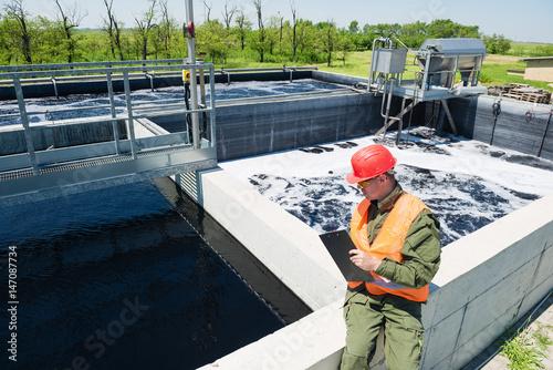 Inżynier kontrolujący jakość wody, napowietrzany zbiornik osadu czynnego w oczyszczalni ścieków