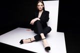 High fashion portrait of young elegant woman in black suit. - 147110351